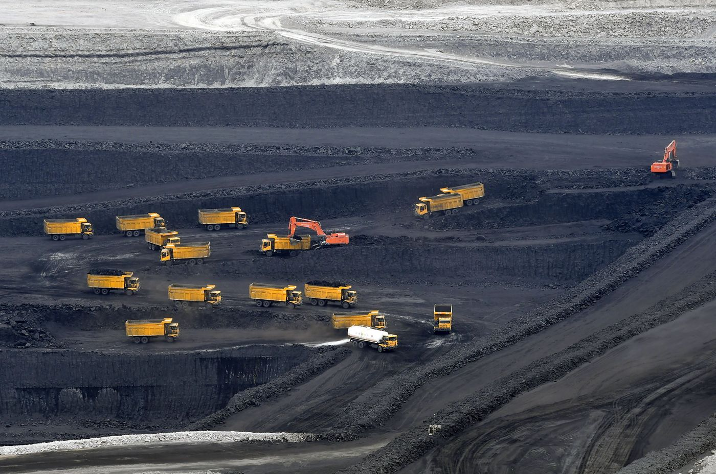 Transport trucks transfer raw coal in pits in Changji Hui Autonomous Prefecture.