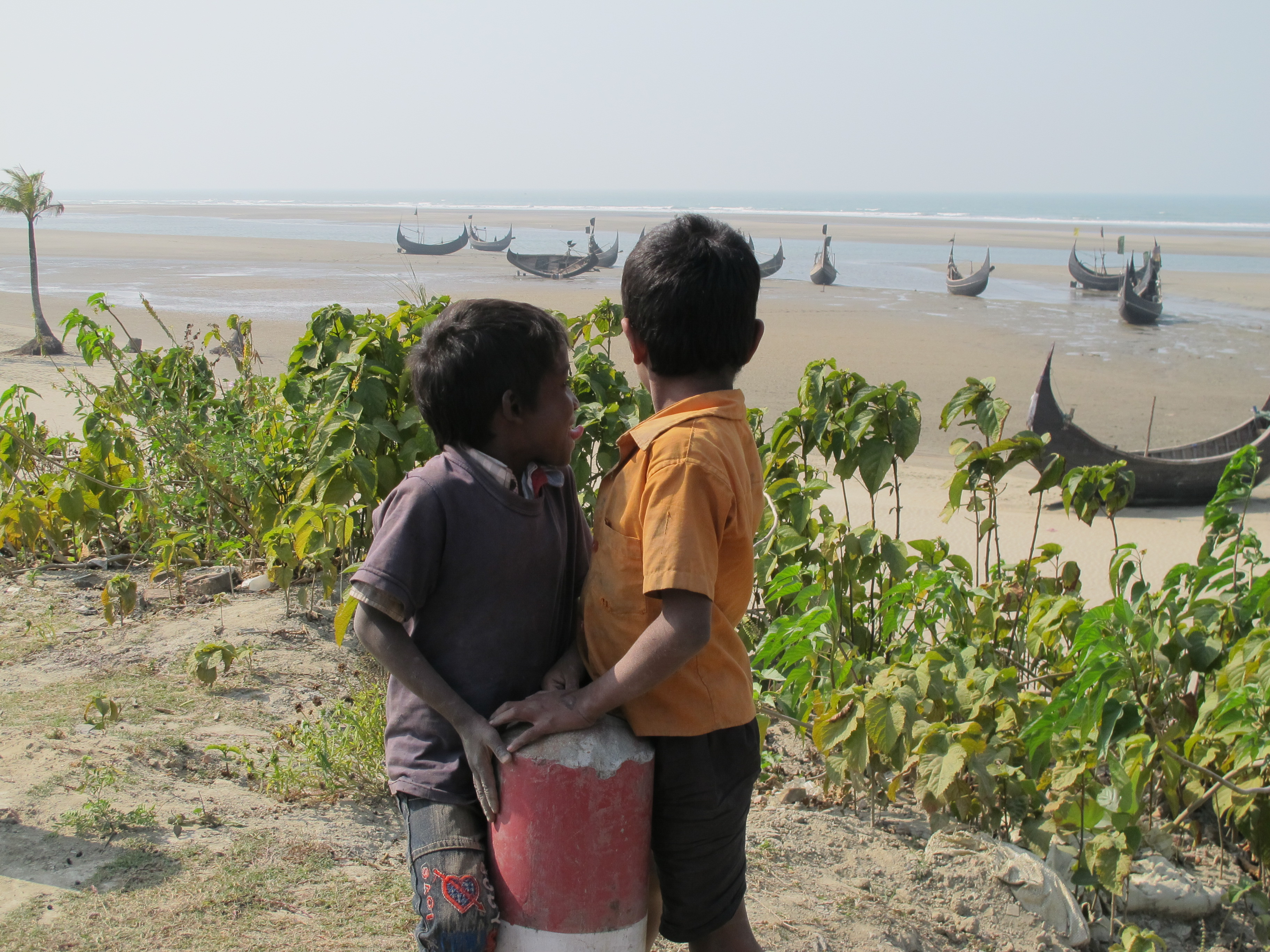 two young boys looking at beached ships