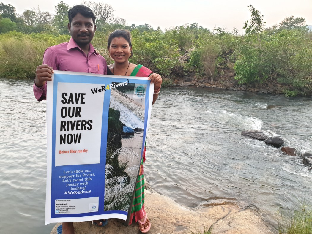 couple holding up poster with the words: save our rivers now