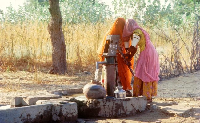 Women drawing water from a hand pump in Rajasthan